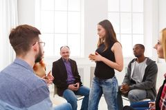 Meeting of support group, therapy session. Patient women standing in circle and telling her problems to therapy group, copy space stock images