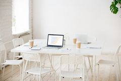 Meeting table with laptops and coffee in empty office room Royalty Free Stock Images