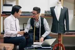 Meeting with tailor. Mature Vietnamese men choosing fabric for the suit at tailors studio Royalty Free Stock Photos