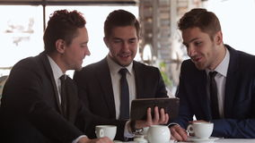 The meeting of three business people. Business lunch in a restaurant, cafe, coffee shop. Group formally dressed men sitting in the interior over lunch. Business stock video footage