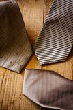 Meeting of ties. Three brown and grey ties on wood Royalty Free Stock Photography