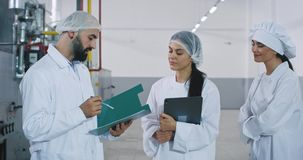 Meeting time between engineer and bakery workers in the big manufacturing engineer explaining the security notes about. The industrial machine stock footage