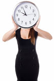 Meeting time will be declared in five minutes. Young woman hiding her face with a wall clock Royalty Free Stock Photos