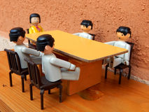 Meeting. Toy figures are talking at the table Stock Images
