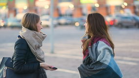 Meeting of two attractive young friends, girls laughing and hugging in the urban street, Steady cam, slow mo shot. Two attractive student gorgeus young girls stock footage
