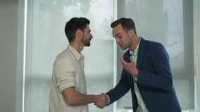 Meeting of two friends. Men shake hands near windows. Caucasian man wearing in blue suit. Mixed race young guy dressed in casual shirt. Happy smiling stock video footage