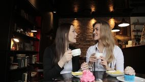 The meeting of two friends over a Cup of tea. Fun conversation, laughter. A conversation between two girls shot in one caffeine of the city with a tripod and stock footage