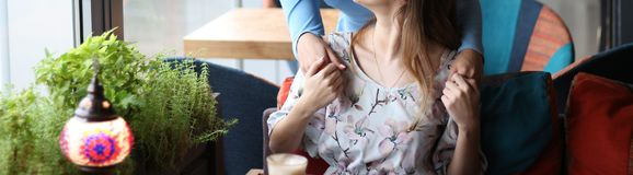 Meeting of two girlfriends in a cafe. one came up behind and hugged to greet another girl. holding hands. Dressed in blue and flowered dresses, there is coffee stock images