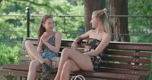 Two young girls in a city enjoying summer in a city park. Meeting of two happy girls. Positive face expressions, emotions, feelings, body language stock video footage