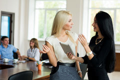 The meeting of two young businesswomen in the office on the back. Ground of team meetings Royalty Free Stock Photos