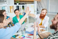 The meeting was a success. Colleagues giving five at the table during a business meeting Royalty Free Stock Photo