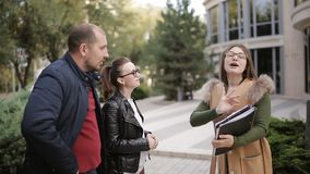 Meeting women realtor and a young couple near the modern design of the building. The realtor and the young couple are discussing the nuances of lease or purchase stock footage