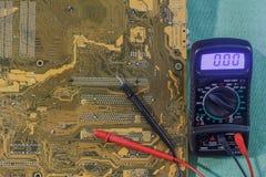 Meetinstrumentmultimeter met geel-bruin gedrukte kringsraad stock foto
