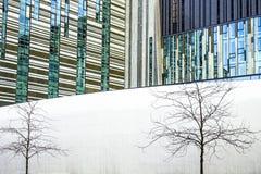 Meetkunde van de stad, moderne gebouwen van glas en metaal, bomen zonder bladeren op een witte achtergrond Modern en abstract arc Stock Foto