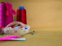 Meetlint, kegels van naaiende draad, een naadschulpzaag en spelden royalty-vrije stock foto's