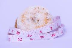 Meetlint rond zoete doughnut op witte achtergrond wordt vastgemaakt die stock afbeelding