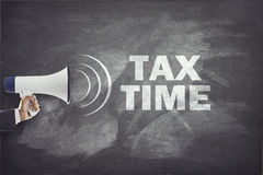 Megáfono con la muestra del tiempo del impuesto en la pizarra Foto de archivo