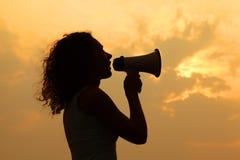 Megáfono de la explotación agrícola de la mujer en la puesta del sol Fotos de archivo