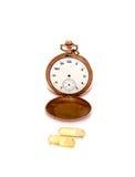 A ômega do óleo de fígado de bacalhau 3 cápsulas do gel na frente do bolso do vintage cronometra Imagens de Stock Royalty Free