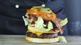 Mega grote hamburger met dubbele kotelet met groenten en sesambroodje, het proces om een hamburger, de chef-kok in zwarte te vorm stock videobeelden