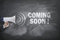 Megafon med att komma snart tecken på svart tavla Fotografering för Bildbyråer