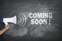 Megafon med att komma snart tecken på svart tavla arkivfoton
