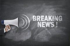 Megafon med breaking newstext på svart tavla Arkivbilder