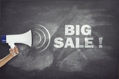 Megafon med det stora försäljningstecknet på svart tavla arkivfoto