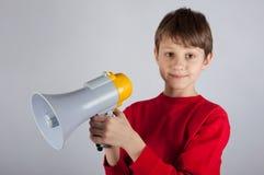 Megafono sveglio della tenuta del ragazzo in sue mani Fotografia Stock Libera da Diritti