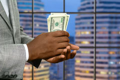 Megalopolis businessman holds money. Afroamerican office manager holding salary. Megalopolis businessman holds money. Warm up your pocket. Fresh and crispy stock photography