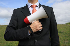 Megaphone. Businessman with a black suit holding a megaphone like gun Royalty Free Stock Photos
