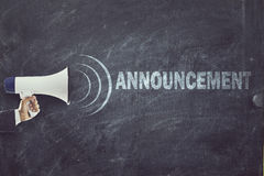 Megaphone with announcement sign on blackboard. Man holding a megaphone in front of blackboard with announcement text Royalty Free Stock Images