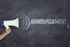 Megaphone with announcement sign on blackboard. Woman holding a megaphone in front of blackboard with announcement text Stock Photos