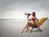 Megaphone on the beach. Woman using megaphone on the beach Royalty Free Stock Photos