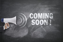 Megaphone with coming soon sign on blackboard Stock Image