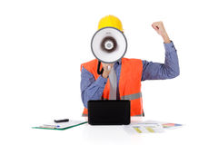Megaphone face, young caucasian man architect. Young caucasian man architect with safety helmet in the office and working with laptop, megaphone in front face royalty free stock images