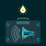 A megaphone in a suitcase in a dark room with a light bulb. Royalty Free Stock Images