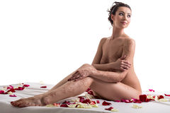 Mehandi Τοποθέτηση Brunette nude στο κρεβάτι με τα πέταλα Στοκ Φωτογραφίες