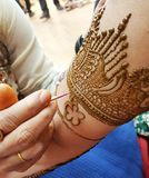 Detailed process of applying intricate pattern Henna on hand. A mehandi applying artist creates wonderful graphic designs on the hands of a bride in India stock image