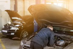 Mehanic die controle doen onder geopende autokap Hulpmiddelen over vuile motorruimte De autodienst en onderhoud gestemd royalty-vrije stock afbeeldingen