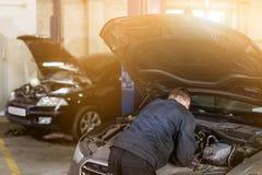 Mehanic robi badania kontrolne pod rozpieczętowanym samochodowym kapiszonem Narzędzia nad brudnym motorowym pokojem Samochodu utr obrazy royalty free