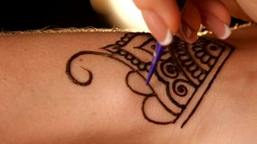 Mehendi drawing process on hand, back light, close stock video footage