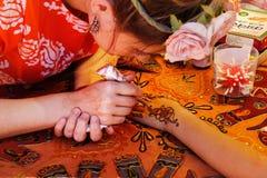 Mehendikonstnär för ung kvinna som målar henna för blom- prydnad på handen på Holi färgfestival i Volgograd Royaltyfri Bild