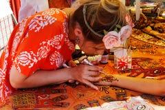 Mehendikonstnär för ung kvinna som målar henna för blom- prydnad på handen på Holi färgfestival i Volgograd Royaltyfria Foton