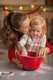 Mehl geschmierte Mutter und Baby, die Plätzchen macht stockbild