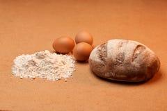 Mehl mit drei Eiern und einem Laib Lizenzfreie Stockbilder
