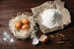 Mehl und Eier auf einem hölzernen Brett Stockbild