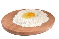 Mehl und Eier auf einem hölzernen runden Vorstand. Stockfotos