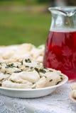 Mehlklöße mit Hüttenkäse auf einer Platte und einem Preiselbeersaft in einem Glaskrug, der auf dem Tisch steht Stockbilder