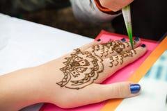 Mehndi application on woman hand, skin decoration Stock Image